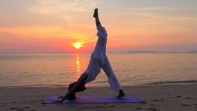 Asiatin-übendes Yoga in dem Sonnenuntergang-Meer stock video