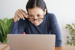 Asiatin arbeitet im Büro Sie trägt Glasaugen und -blicke zum Laptop so ernsthaft stockfotos