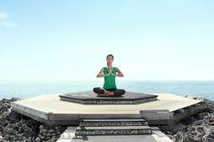 Asiatin auf dem Strand, der Meditation tut Stockfoto