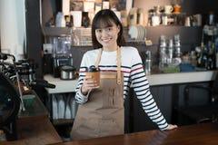 Asiatin barista, das mit einem Tasse Kaffee in ihr lächelnd steht stockfotografie