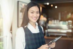 Asiatin barista, das mit Tablette in ihrer Hand lächelt Stockbilder