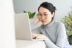 Asiatin bearbeitet einen Laptop im Wohnzimmer Sie sitzt auf dem Boden und Sofa ist Schreibtisch lizenzfreie stockfotografie