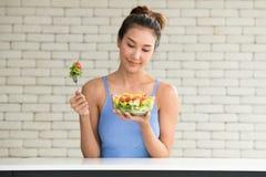 Asiatin in den frohen Lagen mit der Hand, die Salat hält lizenzfreie stockbilder