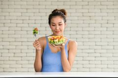 Asiatin in den frohen Lagen mit der Hand, die Salat hält stockbild