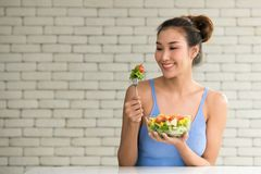 Asiatin in den frohen Lagen mit der Hand, die Salat hält stockfotografie