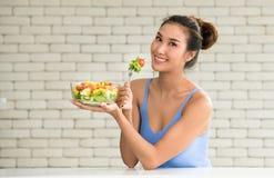 Asiatin in den frohen Lagen mit der Hand, die Salat hält lizenzfreie stockfotos