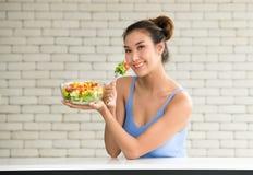 Asiatin in den frohen Lagen mit der Hand, die Salat hält lizenzfreie stockfotografie