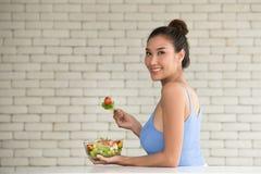 Asiatin in den frohen Lagen mit der Hand, die Salatschüssel hält stockbild