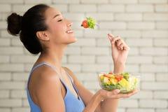 Asiatin in den frohen Lagen mit der Hand, die Salatschüssel hält stockfotos