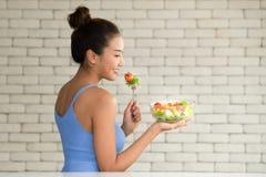 Asiatin in den frohen Lagen mit der Hand, die Salatschüssel hält lizenzfreie stockbilder