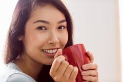 Asiatin, die auf Couch mit Kaffee sich entspannt Stockfotos