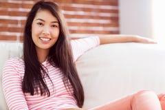 Asiatin, die auf Couch sich entspannt Lizenzfreie Stockfotos