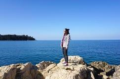 Asiatin, die auf dem Felsen mit adriatisches Seehintergrund steht Lizenzfreie Stockfotos