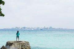 Asiatin, die auf dem Pier am Strand mit Stadt am Hintergrund steht Stockfotos