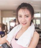 Asiatin, die auf Eignungstretmühle steht lizenzfreie stockfotografie