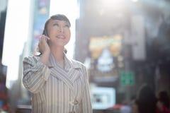 Asiatin, die auf Mobiltelefon in der Stadt spricht Lizenzfreie Stockfotos