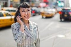 Asiatin, die auf Mobiltelefon in der Stadt spricht Lizenzfreie Stockfotografie