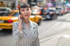 Asiatin, die auf Mobiltelefon in der Stadt spricht Stockbild