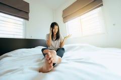 Asiatin, die auf Mobiltelefon im Schlafzimmer sich fühlt ernst spricht lizenzfreie stockfotos