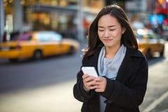 Asiatin, die auf Mobiltelefon simst Stockfotografie