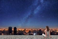 Asiatin, die auf Nachtstadt schaut Stockfotografie