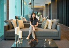 Asiatin, die auf Sofa in der Luxuseigentumswohnung lächelt lizenzfreies stockbild