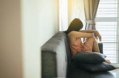Asiatin, die auf Sofa im Wohnzimmer, glaubende Frauen verwirrtes und besorgtes, unerwartetes Schwangerschaftskonzept sitzt stockfotografie