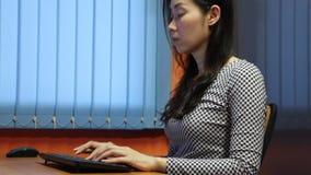 Asiatin, die an Computer schreibt und arbeitet stock footage