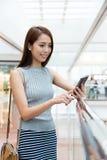 Asiatin, die das Mobiltelefon für Antriebskraft der Status verwendet Stockbilder