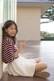 Asiatin, die in der Hand das intelligente Telefon schaut mit Blickkontakt verwendet Stockfotografie