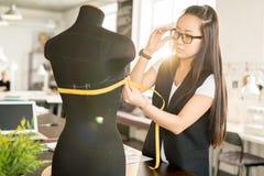 Asiatin, die in der sonnenbeschienen Atelier-Werkstatt arbeitet Lizenzfreies Stockfoto