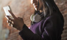 Asiatin, die digitales Gerät und Kopfhörer verwendet stockfoto