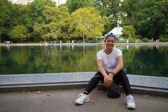 Asiatin, die durch erhaltendes Wasser im Central Park sitzt stockfotografie