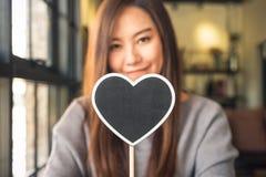 Asiatin, die ein leeres Herzform-Tafelzeichen mit dem Fühlen glücklich und in der Liebe hält lizenzfreie stockfotos