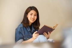Asiatin, die eine Buchweinleseart liest lizenzfreie stockfotografie
