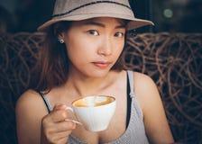 Asiatin, die eine Kaffeetasse hält Lizenzfreie Stockbilder