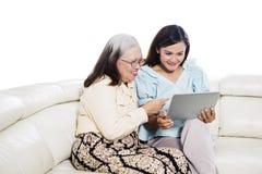 Asiatin, die eine Tablette mit ihrer Mutter verwendet lizenzfreies stockfoto