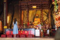 Asiatin, die an einem chinesischen Tempel betet Stockbilder