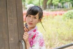 Asiatin, die einen Kimono nahe bei alter Tür trägt Stockfoto