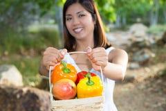 Asiatin, die einen Korb des grünen Pfeffers und der Mango hält Stockfoto