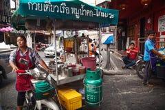 Asiatin, die einen Lebensmittelwarenkorb, Straßenlebensmittel verkaufend fährt Beweglicher thailändischer Lebensmittelverkäufer Stockbild