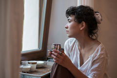 Asiatin, die heraus das Fenster schaut und Tee trinkt Stockbild