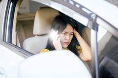 Asiatin, die im Auto sitzt und ihr intelligentes Telefon verwendet Lizenzfreies Stockfoto