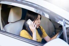 Asiatin, die im Auto sitzt und ihr intelligentes Telefon verwendet Stockbild