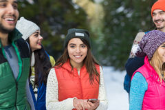 Asiatin, die intelligente Telefon-Schnee-Forest Happy Smiling Young People-Gruppen-gehenden Winter im Freien verwendet Lizenzfreie Stockbilder
