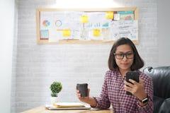 Asiatin, die intelligentes Telefon schaut stockbilder