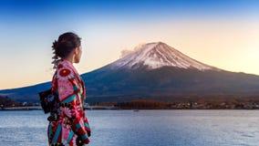 Asiatin, die japanischen traditionellen Kimono an Fuji-Berg trägt Sonnenuntergang am Kawaguchiko See in Japan lizenzfreies stockbild
