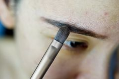 Asiatin, die Kosmetikmake-up, Augenbrauenschablonenzeichnung anwendet stockfotografie