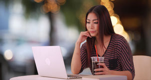 Asiatin, die Laptop am Restaurant verwendet stockfotos