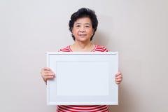 Asiatin, die leeren weißen Bilderrahmen in der Atelieraufnahme, SP hält Stockfotos